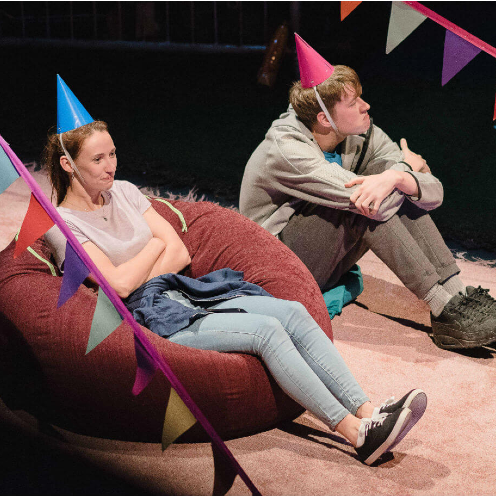 two young people sitting on bean bags wearing party hats